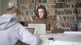 Δύο αρσενικές και γυναίκες σπουδαστές που μελετούν στη βιβλιοθήκη απόθεμα βίντεο