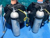 Δύο αρσενικοί δύτες στα μαύρα αδιάβροχα κοστούμια κατάδυσης με τα λαμπρά μεταλλικά κουτιά αργιλίου μετάλλων προετοιμάζονται να βο Στοκ Φωτογραφία