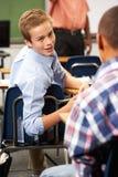 Δύο αρσενικοί μαθητές που μιλούν στην κατηγορία στοκ εικόνα