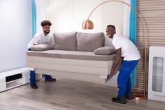 Δύο αρσενικοί μετακινούμενοι που τοποθετούν τον καναπέ στοκ φωτογραφίες με δικαίωμα ελεύθερης χρήσης