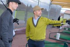 Δύο αρσενικοί παίκτες γκολφ που φαίνονται προς τα εμπρός Στοκ Φωτογραφία