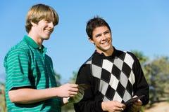 Δύο αρσενικοί παίκτες γκολφ που στέκονται το ένα δίπλα στο άλλο Στοκ Φωτογραφίες