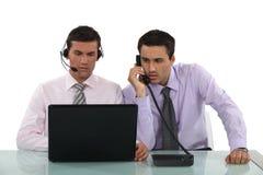 Δύο αρσενικοί τηλεφωνικοί χειριστές στοκ εικόνα με δικαίωμα ελεύθερης χρήσης