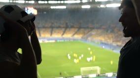 Δύο αρσενικοί φίλοι δίνουν υψηλός-πέντε στο στάδιο, οι οπαδοί ποδοσφαίρου χαίρονται τη νίκη ομάδων φιλμ μικρού μήκους