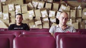 Δύο αρσενικοί φίλοι κάθονται στη σειρά των πορφυρών καρεκλών με τα κεν απόθεμα βίντεο