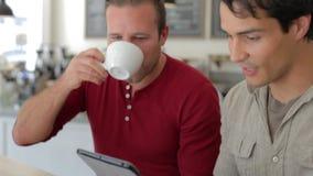 Δύο αρσενικοί φίλοι στη καφετερία που εξετάζουν την ψηφιακή ταμπλέτα απόθεμα βίντεο