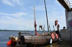 Δύο αρχαίες ξύλινες βάρκες - βάρκες στη σύγχρονη αποβάθρα Στοκ Εικόνες