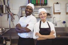 Δύο αρχιμάγειρες που στέκονται με τα όπλα που διασχίζονται στην εμπορική κουζίνα στοκ φωτογραφίες