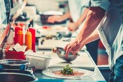 Δύο αρχιμάγειρες στο ομοιόμορφο να προετοιμαστεί εύγευστο πιάτο Στοκ εικόνα με δικαίωμα ελεύθερης χρήσης