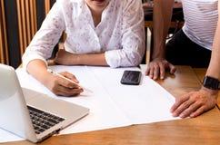 Δύο αρχιτέκτονες που συζητούν τα σχεδιαγράμματα με το τηλέφωνο lap-top και κυττάρων Στοκ Εικόνες