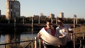 Δύο αρχιτέκτονες στέκονται στο εργοτάξιο, ο ποταμός και εξετάζουν ένα σχέδιο για την οικοδόμηση ενός εμπορικού κέντρου απόθεμα βίντεο