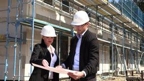 Δύο αρχιτέκτονες στα άσπρα κράνη συζητούν ένα σχέδιο σε ένα εργοτάξιο οικοδομής φιλμ μικρού μήκους