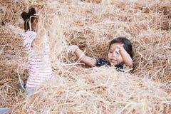Δύο ασιατικά κορίτσια παιδιών που έχουν τη διασκέδαση που παίζει με το σωρό σανού από κοινού Στοκ φωτογραφίες με δικαίωμα ελεύθερης χρήσης