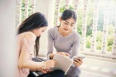 Δύο ασιατικά κορίτσια που διαβάζουν το βιβλίο από κοινού η εκπαίδευση έννοιας βιβλίων απομόνωσε παλαιό Στοκ φωτογραφία με δικαίωμα ελεύθερης χρήσης