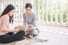 Δύο ασιατικά κορίτσια που διαβάζουν το βιβλίο από κοινού η εκπαίδευση έννοιας βιβλίων απομόνωσε παλαιό Στοκ Εικόνα