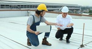 Δύο ασιατικοί μηχανικοί που κάθονται στη στέγη απόθεμα βίντεο