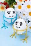 Δύο αστεία αυγά χαμόγελου στις στάσεις και λουλούδια για Πάσχα Στοκ εικόνα με δικαίωμα ελεύθερης χρήσης