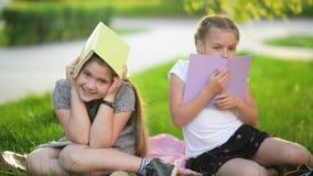Δύο αστεία κορίτσια παίζουν με τα βιβλία Χαμογελούν και έχουν πολλή διασκέδαση Ο καιρός έχει ήλιο φιλμ μικρού μήκους