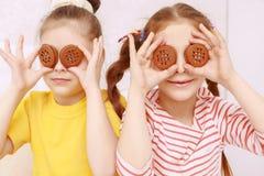 Δύο αστεία κορίτσια που θέτουν με τα μπισκότα Στοκ φωτογραφία με δικαίωμα ελεύθερης χρήσης