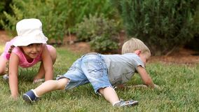 Δύο αστεία παιδιά έχουν τη διασκέδαση στο πάρκο που βρίσκεται στη χλόη απόθεμα βίντεο