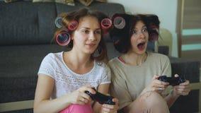Δύο αστεία παιχνίδια κονσολών παιχνιδιού γυναικών με το gamepad και έχουν τη διασκέδαση στο σπίτι Στοκ φωτογραφίες με δικαίωμα ελεύθερης χρήσης