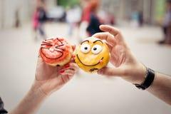 Δύο αστεία donuts στα ανθρώπινα και χέρια της γυναίκας Στοκ Εικόνες