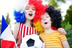 Δύο αστείες μικρές αδελφές που υποστηρίζουν και ενθαρρυντικές οι εθνικές ομάδες ποδοσφαίρου τους Στοκ εικόνα με δικαίωμα ελεύθερης χρήσης