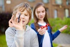 Δύο αστείοι φίλοι που παίζουν με fidget τους κλώστες στην παιδική χαρά Δημοφιλές πίεση-ανακουφίζοντας παιχνίδι για τα σχολικούς π Στοκ Εικόνες