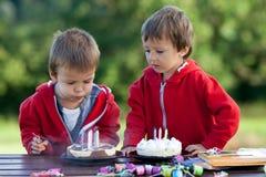Δύο λατρευτά αγόρια με τα κέικ, υπαίθρια, γενέθλια εορτασμού Στοκ Φωτογραφία
