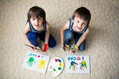 Δύο λατρευτά αγόρια, που προετοιμάζουν το δώρο ημέρας πατέρων για τον μπαμπά, ζωγραφική Στοκ Εικόνα