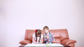 Δύο λατρευτά ευτυχή παιδιά που σύρουν με τα κραγιόνια στο playschool κορίτσι με το κάτω σύνδρομο αποκατάσταση των ατόμων με ειδικ απόθεμα βίντεο