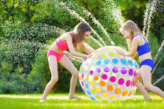 Δύο λατρευτά μικρά κορίτσια που παίζουν με τη διογκώσιμη σφαίρα παραλιών σε ένα κατώφλι την ηλιόλουστη θερινή ημέρα Χαριτωμένα πα Στοκ Εικόνες
