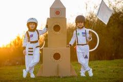 Δύο λατρευτά παιδιά, που παίζουν στο πάρκο στο ηλιοβασίλεμα, που ντύνεται όπως το α Στοκ Φωτογραφία