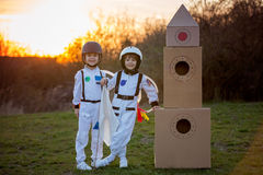 Δύο λατρευτά παιδιά, που παίζουν στο πάρκο στο ηλιοβασίλεμα, που ντύνεται όπως το α Στοκ Φωτογραφίες