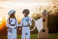 Δύο λατρευτά παιδιά, που παίζουν στο πάρκο στο ηλιοβασίλεμα, που ντύνεται όπως το α Στοκ φωτογραφία με δικαίωμα ελεύθερης χρήσης
