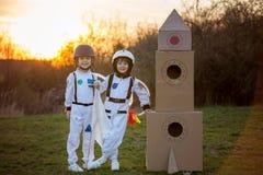 Δύο λατρευτά παιδιά, που παίζουν στο πάρκο στο ηλιοβασίλεμα, που ντύνεται όπως το α Στοκ Εικόνες