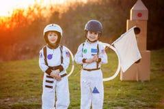 Δύο λατρευτά παιδιά, που παίζουν στο πάρκο στο ηλιοβασίλεμα, που ντύνεται όπως το α Στοκ εικόνες με δικαίωμα ελεύθερης χρήσης