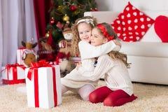 Δύο λατρευτά σγουρά κορίτσια που παίζουν με το κιβώτιο δώρων Στοκ Εικόνες