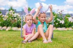 Δύο λατρευτές μικρές αδελφές που φορούν τα αυτιά λαγουδάκι την ημέρα Πάσχας υπαίθρια στοκ φωτογραφίες