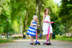 Δύο λατρευτές μικρές αδελφές που φορούν τα όμορφα φορέματα που οδηγούν τα μηχανικά δίκυκλά τους Στοκ Φωτογραφία