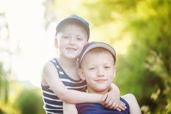Δύο λατρευτοί μικροί αδελφοί που γελούν και που αγκαλιάζουν την ηλιόλουστη θερινή ημέρα Στοκ φωτογραφία με δικαίωμα ελεύθερης χρήσης