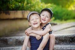 Δύο λατρευτοί μικροί αδελφοί που γελούν και που αγκαλιάζουν τη θερμή και ηλιόλουστη ημέρα Στοκ φωτογραφία με δικαίωμα ελεύθερης χρήσης