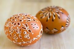 Δύο αυγά Πάσχας με τα διάφορα κέρινα έργα ζωγραφικής και τις μικρές τρύπες, ξύλινο υπόβαθρο στοκ φωτογραφίες