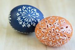 Δύο αυγά Πάσχας με τα διάφορα κέρινα έργα ζωγραφικής και τις μικρές τρύπες, ξύλινο υπόβαθρο στοκ φωτογραφία