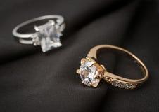 Δύο δαχτυλίδια κοσμήματος με τα διαμάντια στο μαύρο ύφασμα, μαλακή εστίαση Στοκ Φωτογραφίες