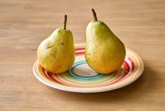 Δύο αχλάδια στο πιάτο χρώματος Στοκ εικόνες με δικαίωμα ελεύθερης χρήσης