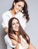 Δύο αδελφές ζευγαρώνουν την τοποθέτηση, κάνοντας τη φωτογραφία selfie, ντυμένο ίδιο άσπρο πουκάμισο, διαφορετικοί φίλοι hairstyle Στοκ εικόνες με δικαίωμα ελεύθερης χρήσης