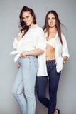 Δύο αδελφές ζευγαρώνουν την τοποθέτηση, κάνοντας τη φωτογραφία selfie, ντυμένο ίδιο άσπρο πουκάμισο, διαφορετικοί φίλοι hairstyle Στοκ Εικόνες