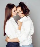 Δύο αδελφές ζευγαρώνουν την τοποθέτηση, κάνοντας τη φωτογραφία selfie, ντυμένο ίδιο άσπρο πουκάμισο, διαφορετικοί φίλοι hairstyle Στοκ Φωτογραφία