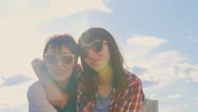 Δύο αδελφές με τα γυαλιά που αγκαλιάζουν και που γελούν απόθεμα βίντεο